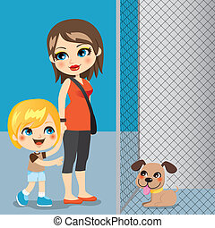 Little boy with mother adopting a cute dog from animal shelter