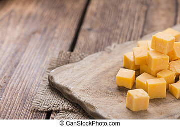 Pieces of Cheddar (close-up shot) on an old wooden table