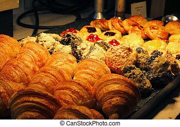 croissant bread, cinnamon roll and fruit danish dessert on buffet line