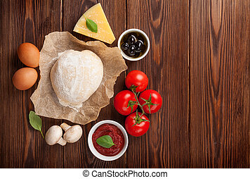 Pizza cooking ingredients. Dough, vegetables and spices. Top view with copy space