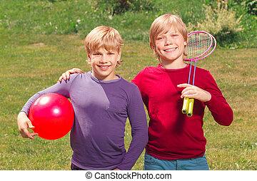 Pleasant smiling boys holding sport equipment