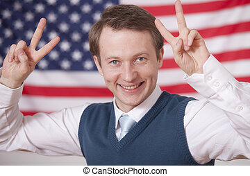politician with victory signs over american flag
