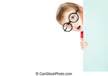 Portrait of a cute boy in spectacles peeking around the white board. Isolated over white.