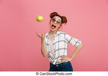 Portrait of a happy young girl in sunglasses with green apple