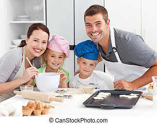 Portrait of a joyful family cooking littles cakes in the kitchen