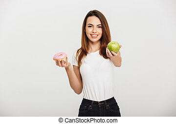 Portrait of a smiling young girl giving green apple