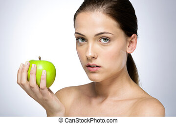 Portrait of a young beautiful girl with green apple