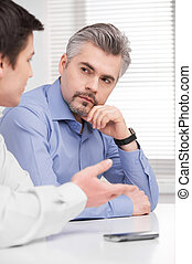 Portrait of serious middle aged business man. Sitting and listening to young adult colleague