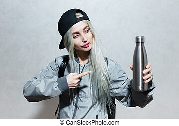 Portrait of young blonde girl, point with finger at steel thermo bottle in hand.