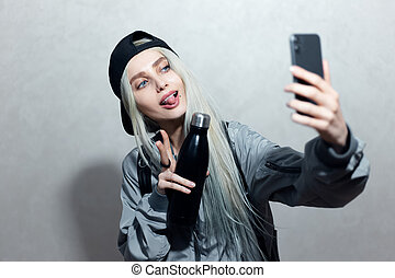 Portrait of young blonde girl with thermo bottle in hand take a selfie photo on smartphone.