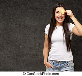 portrait of young woman holding a potato chip in front of her eye against a grunge wall