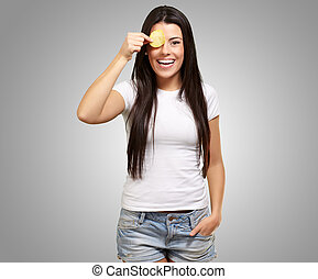 portrait of young woman holding a potato chip in front of her eye over grey