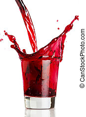 A red liquid being poured into, and splashing over, a glass.