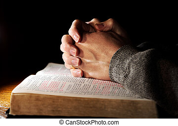 A man's hands clasped in prayer over a Holy Bible on a table with dramatic lighting (shallow focus).
