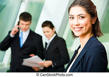 Face of pretty professional with charming smile on the background of colleagues