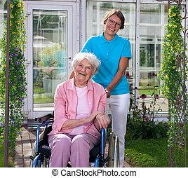 Professional carer behind happy elderly woman