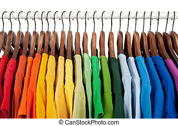 Rainbow colors. Choice of casual clothes on wooden hangers, isolated on white.