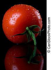 Fresh raw tomato with reflection on black background