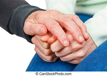 Wrinkled reassuring hand on young anxious hands