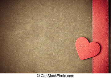 Valentine's day. Red wooden decorative heart love symbol on beige cloth textile background with ribbon. Blank copy space