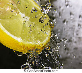 Water drops falling onto a lemon - focus is on the water drops