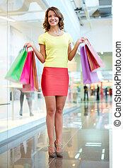 Vertical portrait of a female shopper doing her regular shopping