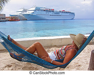 A woman rests on a hammock and views cruise ships across the harbor