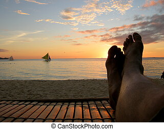 Relaxing on a beach chair at sunset.