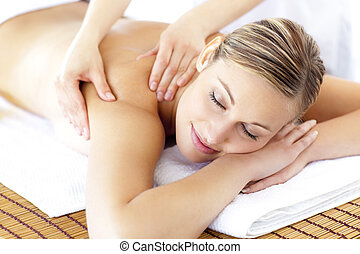 Relaxed smiling woman receiving a back massage in a spa