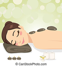 Beautiful brunette enjoying relaxing hot stone massage with soft light candles at beauty parlor