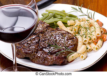 A grilled rib eye steak with vegetables, pasta and red wine