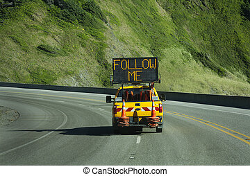 road construction ahead you must follow the pilot truck on a road through the mountains. lighted sign says follow me.