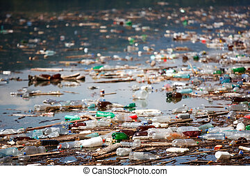 many plastic bottles and trash floating on water lake, shallow deep of field