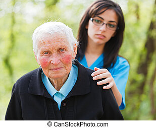 Sad elderly woman and caring nurse outdoors.