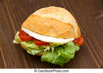 Sandwich with cheese and tomatoes on wooden table