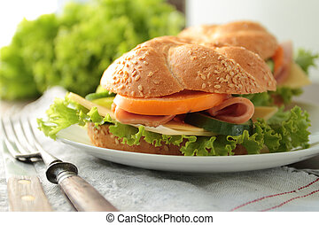 Sandwich with ham, cheese and fersh vegetables on a plate