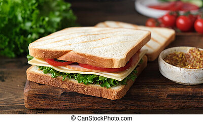 Sandwich with ham, cheese, tomato and lettuce