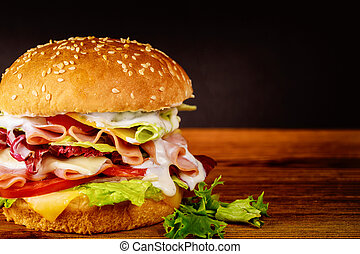 Sandwich with ham, lettuce, cheese and tomato.