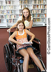 Two school girls at the library. One is in a wheelchair.