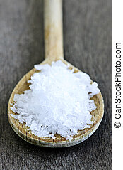 Sea salt on wooden spoon over wooden table background