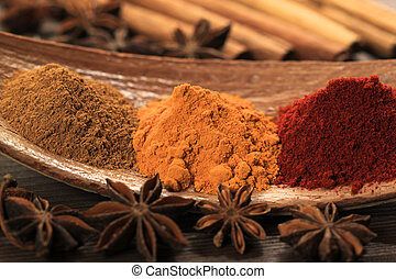 Cooking ingredients - warm colours of herbs and spices. Turmeric and cayenne pepper, plus aniseed and cinammon sticks.