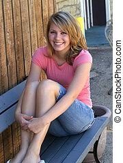 blonde brown eyed teen sitting outside on bench in summer smiling