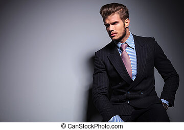 seated young fashion model in suit and tie is looking away to his side