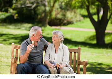 Senior couple eating an ice cream on a bench