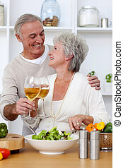 Senior couple in love eating a salad in the kitchen