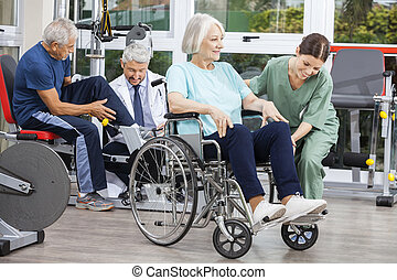 Disabled senior people being assisted by physiotherapists in rehab fitness center
