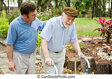 Senior man struggling to us a walker. His adult son is helping him.