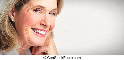 Senior smiling woman portrait. Over grey background.
