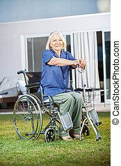 Senior Woman Sitting On Wheelchair At Nursing Home Lawn