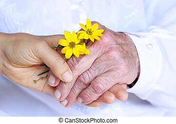 Senior Lady and Young Woman Holding Hands - Giving Flowers (Friendship, Care, Service)